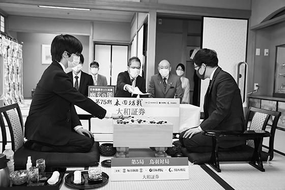 이틀거리바둑 둘째날 대국 개시 장면. 입회인 야마시로 히로시 九단(가운데)이 시바노 九단의 첫날 봉수점을 적은 기보용지를 이야마 九단(오른쪽)에게 확인케 하고 있다.